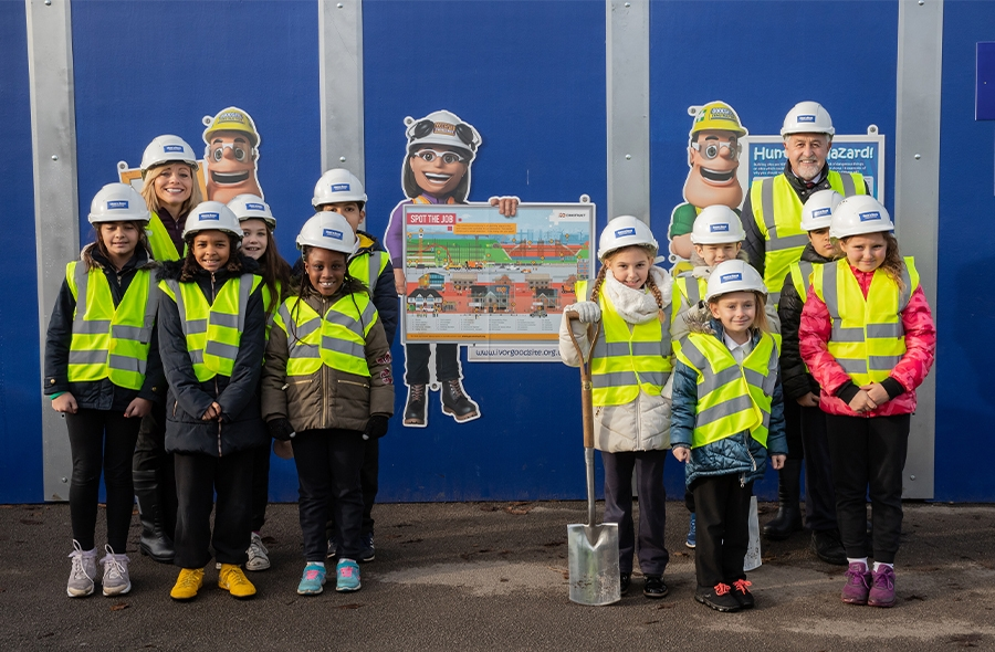 Children learning about the works involved on the project from the side of the hoardings